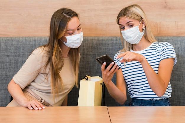 Młode kobiety razem sprawdzanie telefonu komórkowego
