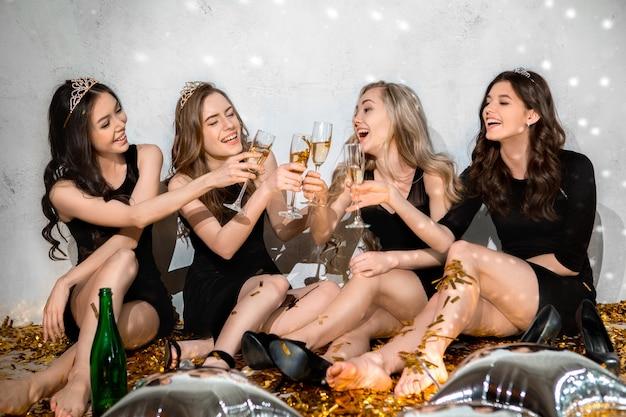 Młode kobiety razem świętują wieczór panieński na białym tle