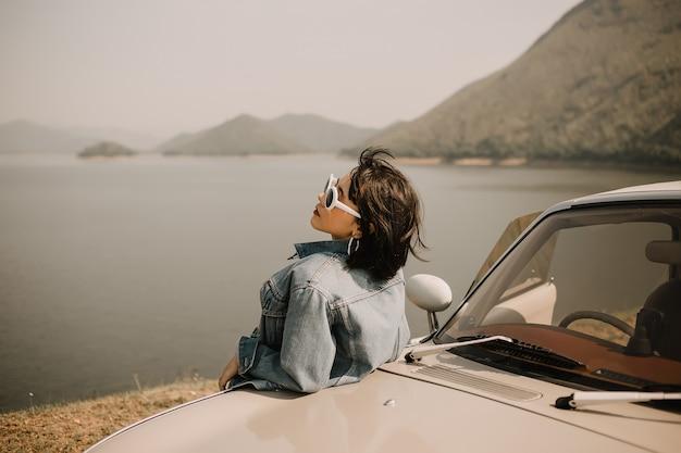 Młode kobiety relaksuje na jeziorze. pojedzie nad jezioro klasycznym samochodem. ona nosi okulary przeciwsłoneczne.