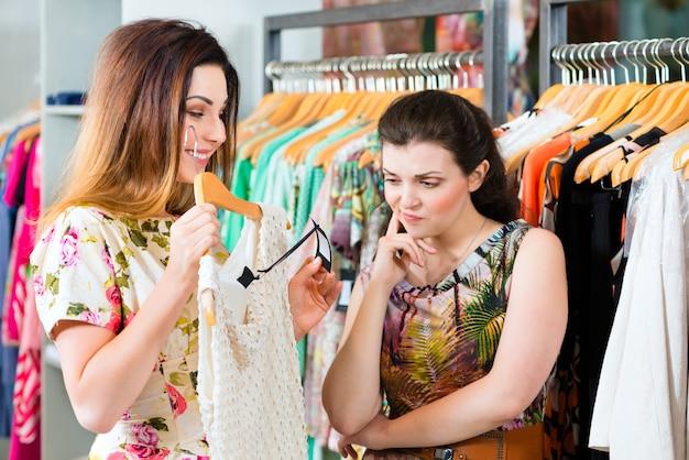 Młode kobiety robi zakupy w moda wydziałowym sklepie