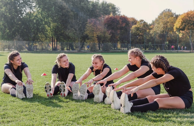 Młode kobiety robią ćwiczenia rozgrzewkowe