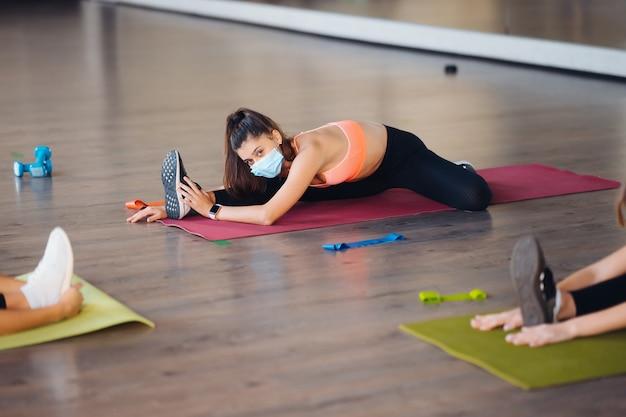 Młode kobiety robią push up ćwiczenia w pokoju w godzinach porannych. szczupłe dziewczyny noszące maski, by chronić pandemię choroby covid-19 i dystans społeczny.