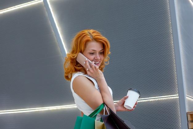 Młode kobiety rozmawia przez telefon z pakietami zakupy w nowoczesnym centrum handlowym. koncepcja zakupów. koncepcja czarny piątek. szczęśliwe kobiety. trzymanie paczek.