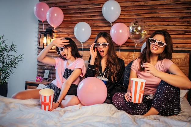 Młode kobiety rozpraszają emocje na twarzy. oglądają film przez specjalne okulary. kobiety siedzą na łóżku w świątecznym pokoju. mają imprezę w piżamie.