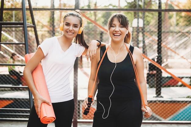 Młode kobiety śmieją się podczas uprawiania sportu z koleżanką w godzinach porannych