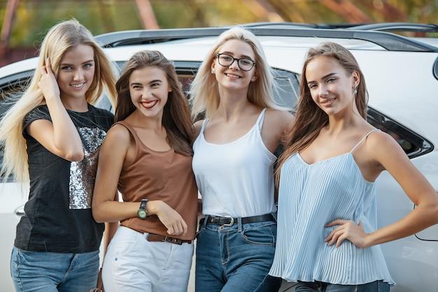 Młode kobiety stojące w pobliżu samochodu