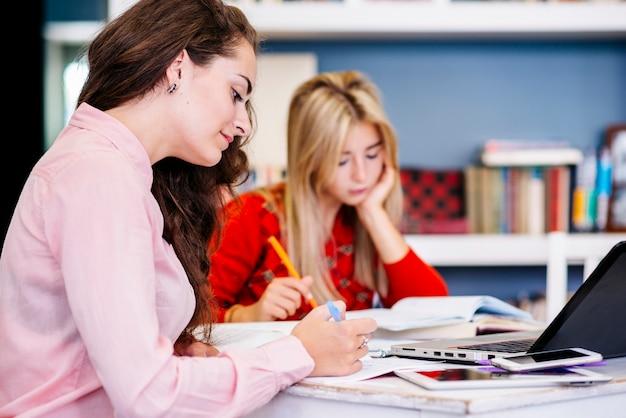 Młode kobiety studiuje przy stołem
