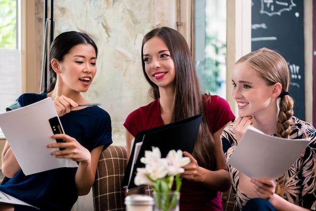 Młode kobiety trzyma kartoteki w sklep z kawą