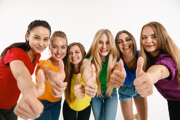 Młode kobiety ubrane w kolory flagi lgbt na białej ścianie. kaukaskie modelki w jasnych koszulach.