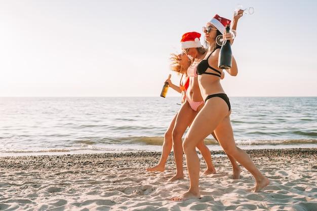 Młode kobiety w bikini i czapki mikołaja