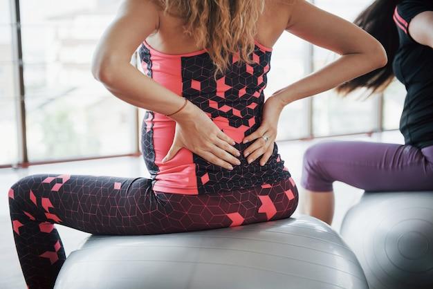 Młode kobiety w ciąży siedzi na piłce do ćwiczeń na siłowni