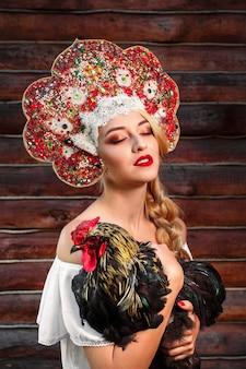 Młode kobiety w czerwonym nakryciu głowy i rosyjskim stylu ludowym trzymają koguta ptaka na ciemnym drewnianym. rosyjska bajka
