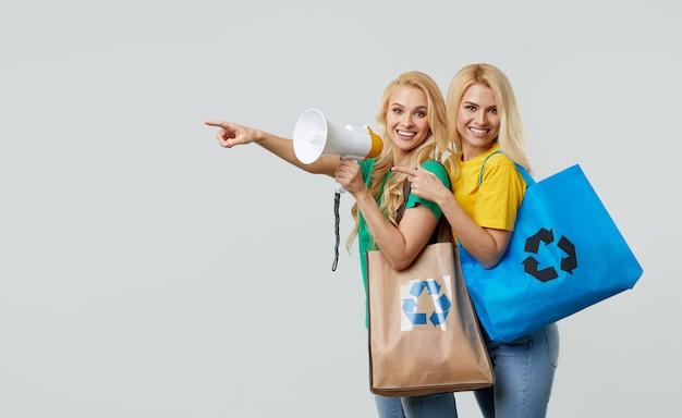 Młode kobiety w zwykłych ubraniach trzymają ekologiczne torby z recyklingu i krzyczą do megafonu, żeby przetwarzać odpady z tworzyw sztucznych. wskaż w lewo, aby opróżnić miejsce na tekst.