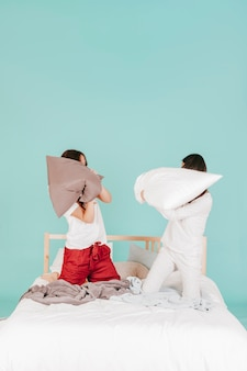 Młode kobiety walczy z poduszkami na łóżku