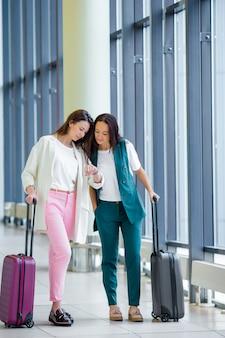 Młode kobiety z bagażem w lotnisku międzynarodowym odprowadzenie z jej bagażem. pasażerowie linii lotniczych w poczekalni na lotnisku czekają na samolot