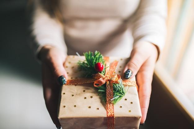 Młode kobiety z brokatowymi paznokciami trzyma pudełko na prezent świąteczny