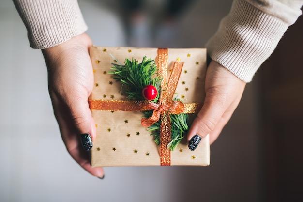 Młode kobiety z czarnymi brokatowymi paznokciami trzymającymi pudełko na prezent świąteczny