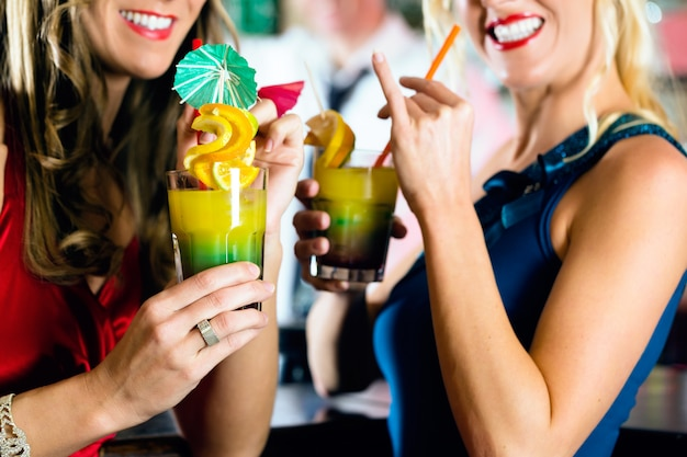 Młode kobiety z koktajlami w barze lub klubie