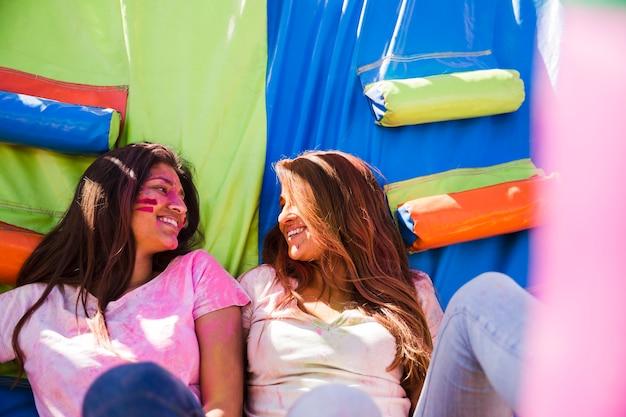 Młode kobiety z kolorem holi na twarzy patrząc na siebie