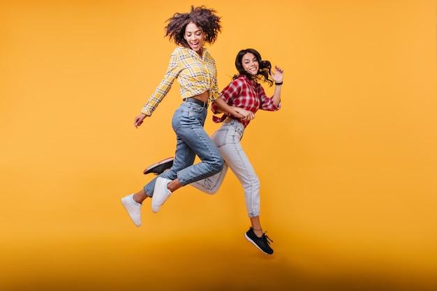Młode kobiety z kręconymi włosami biegają. modelki w streetwearach pozują w skoku