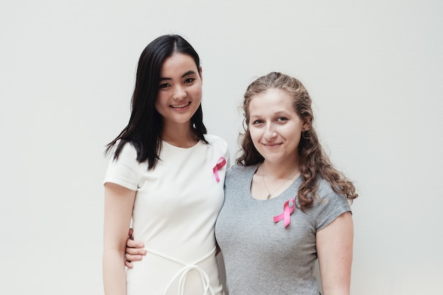 Młode kobiety z różowymi wstążkami