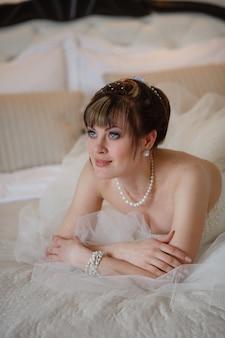 Młode kobiety z suknią ślubną w bardzo jasnym pokoju