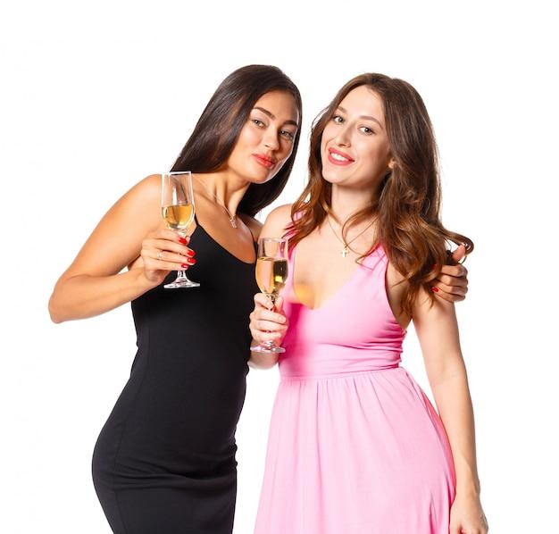 Młode kobiety z szampańskimi szkłami przy świętowaniem