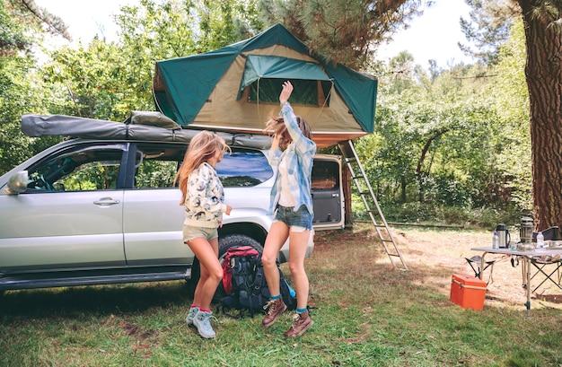 Młode koleżanki bawią się na kempingu w lesie. koncepcja czasu wolnego i przyjemności.