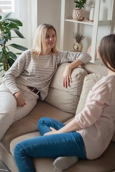 Młode koleżanki rozmawiają, uśmiechają się razem, siedzą na kanapie a