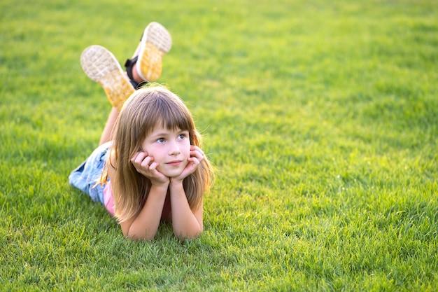 Młode ładne dziecko dziewczynka ustanawiające na zielonej trawie trawnik w ciepły letni dzień.