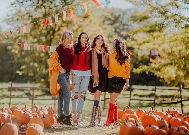 Młode ładne kobiety składające się z czterech osób pozuje na odkrytym rynku dyni.
