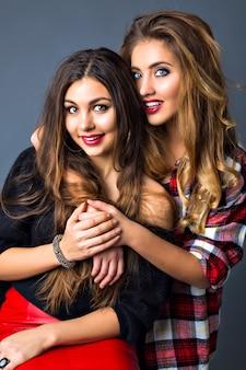 Młode ładne pary kobiet pozujących, modny elegancki portret, brunetka i blondynka, uściski najlepszych przyjaciół, dopasowane kolorystycznie ubrania, jasny seksowny makijaż, długie włosy.