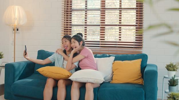 Młode lesbijskie kobiety lgbtq dobierają selfie w domu.