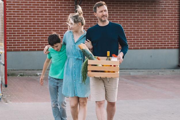 Młode małżeństwo pochodzi z supermarketu z artykułami spożywczymi. koncepcja materiałów ekologicznych. styl życia