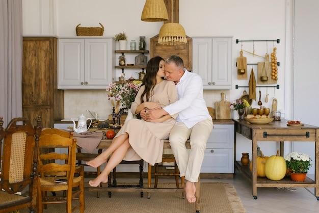 Młode małżeństwo przytula się, siedząc na stole w kuchni. mąż ściska ciężarną żonę, kładąc ręce na jej wielkim brzuchu. styl życia rodziny