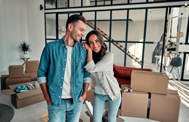 Młode małżeństwo rozpakowujące rzeczy z pudeł w salonie przeprowadzka kupno domu