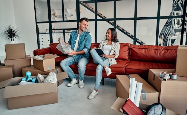 Młode małżeństwo rozpakowujące rzeczy z pudeł w salonie w domu. szczęśliwy mąż i żona dobrze się bawią, nie mogą się doczekać nowego domu. przeprowadzka, kupno domu, koncepcja mieszkania.