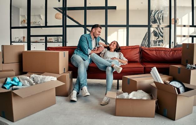 Młode małżeństwo siedzi na kanapie w salonie w domu. szczęśliwy mąż i żona dobrze się bawią, nie mogą się doczekać nowego domu. przeprowadzka, kupno domu, koncepcja mieszkania.