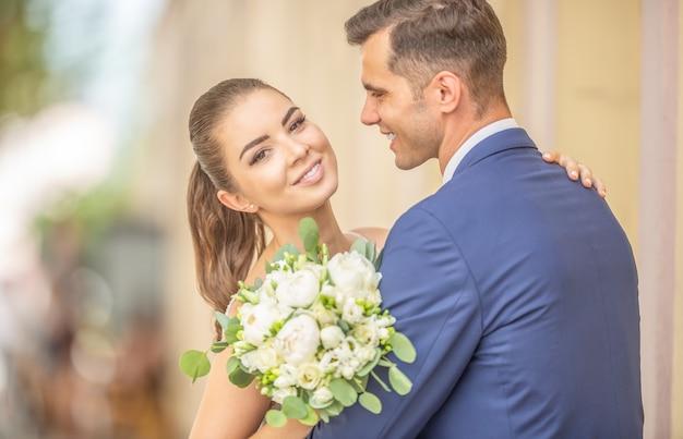 Młode małżeństwo tańczy pierwszy taniec po ceremonii ślubnej ze wspaniałymi kwiatami.