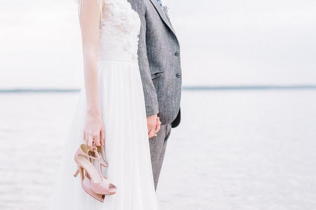 Młode małżeństwo, trzymając się za ręce przed horyzontem. panna młoda trzyma różowe buty na wysokim obcasie