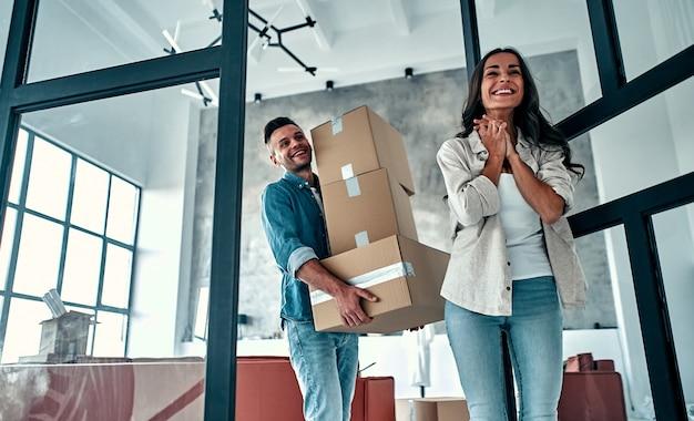 Młode małżeństwo w salonie w domu rozpakowuje pudła z rzeczami. szczęśliwy mąż i żona dobrze się bawią, nie mogą się doczekać nowego domu. przeprowadzka, kupno domu, koncepcja mieszkania.