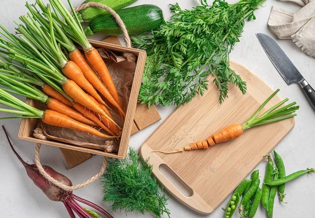 Młode marchewki, cukinia, buraki i groch na szarym tle. gotowanie dania warzywnego.