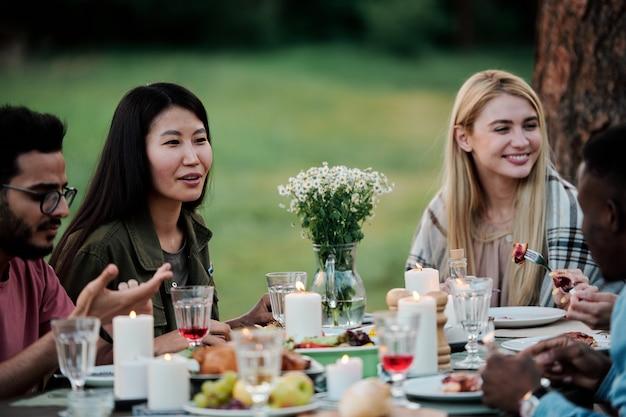 Młode międzykulturowe kobiety rozmawiają ze swoimi chłopakami przy stole z domowym jedzeniem, napojami i palącymi świecami w naturalnym środowisku