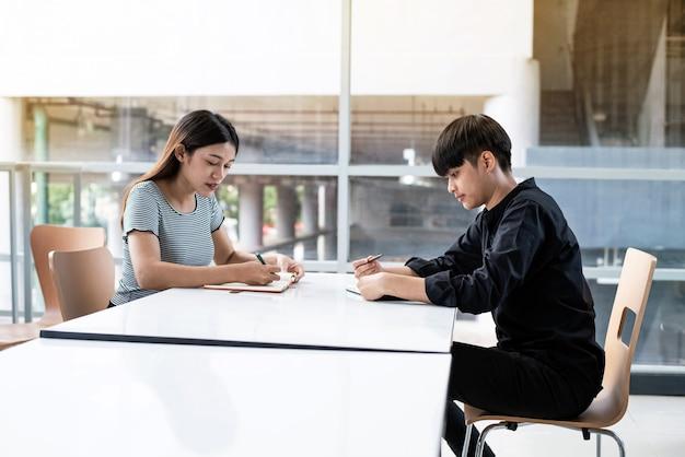 Młode nastolatki razem odrabiające lekcje w sali konferencyjnej