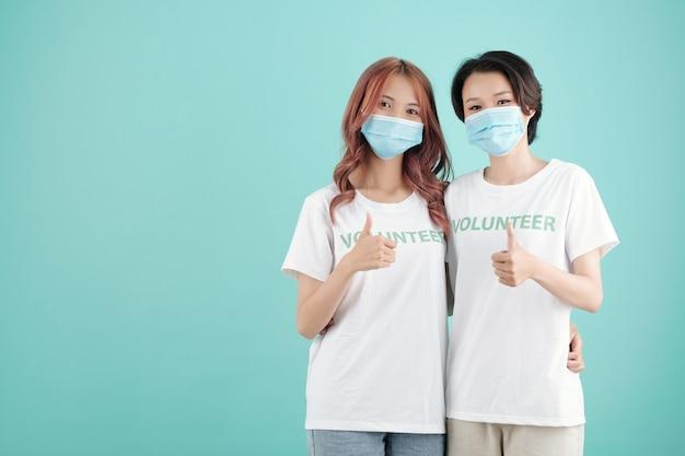 Młode ochotniczki w medycznych maskach przytulające się i pokazujące kciuk w górę, odizolowane na turkusie