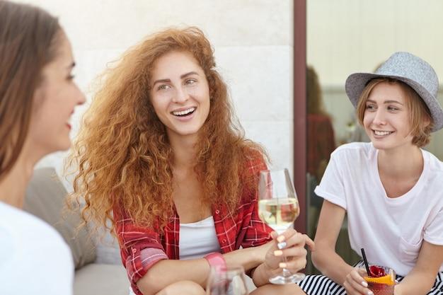 Młode panie siedzą razem, pijąc wino i koktajle