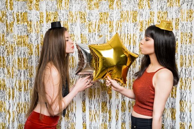 Młode panie w strojach wieczorowych z balonami