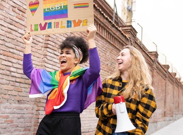 Młode pary kobiet przytulających się pod tęczową flagą w kolorowych maskach na imprezie gay pride - lgbt and love concept -