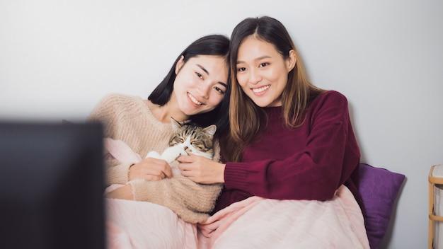 Młode piękne azjatyckie kobiety para lesbijek razem oglądać telewizję z kotem w sypialni.