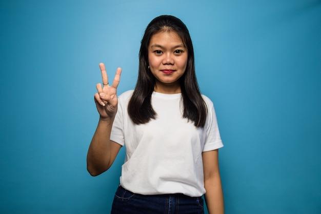 Młode piękne azjatyckie kobiety używają białej koszulki z niebieskim na białym tle dwa znak 2